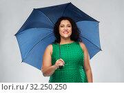 Купить «happy woman in green dress with blue umbrella», фото № 32250250, снято 15 сентября 2019 г. (c) Syda Productions / Фотобанк Лори