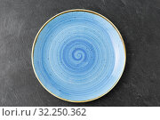 Купить «close up of blue ceramic plate on slate background», фото № 32250362, снято 5 апреля 2018 г. (c) Syda Productions / Фотобанк Лори