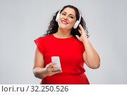 Купить «woman in headphones listens to music on smartphone», фото № 32250526, снято 15 сентября 2019 г. (c) Syda Productions / Фотобанк Лори