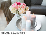 Купить «candles burning on table and flowers at cozy home», фото № 32250654, снято 11 апреля 2019 г. (c) Syda Productions / Фотобанк Лори