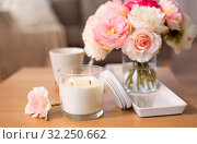 Купить «burning candle and flower bunch on table at home», фото № 32250662, снято 12 апреля 2019 г. (c) Syda Productions / Фотобанк Лори