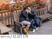 Купить «Young man and woman whisper about something and laugh while sitting on a bench outdoors», фото № 32251178, снято 20 сентября 2019 г. (c) Евгений Харитонов / Фотобанк Лори