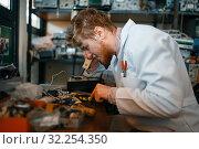 Купить «Strange scientist works with soldering iron in lab», фото № 32254350, снято 17 июня 2019 г. (c) Tryapitsyn Sergiy / Фотобанк Лори