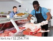 Купить «African American male butcher processing carcase of lamb», фото № 32254714, снято 20 апреля 2018 г. (c) Яков Филимонов / Фотобанк Лори
