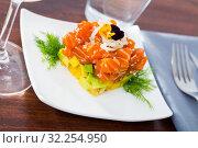 Купить «Cube of delicious salmon tartare garnish with avocado on plate at cafe», фото № 32254950, снято 22 ноября 2019 г. (c) Яков Филимонов / Фотобанк Лори