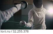 Купить «Two young women fencers having a training in the gym - a woman pokes at the opponent», видеоролик № 32255378, снято 1 апреля 2020 г. (c) Константин Шишкин / Фотобанк Лори