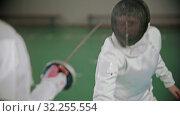 Купить «Two young women in white costumes at fencing training in the school gym», видеоролик № 32255554, снято 1 апреля 2020 г. (c) Константин Шишкин / Фотобанк Лори