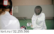 Two young women in protective costumes at fencing training in the school gym - one woman attacks and another defends. Стоковое видео, видеограф Константин Шишкин / Фотобанк Лори