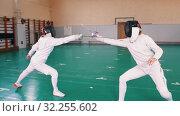 Купить «Two young women in white protective suits having a fencing training in the school gym», видеоролик № 32255602, снято 10 апреля 2020 г. (c) Константин Шишкин / Фотобанк Лори