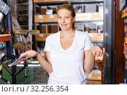Купить «Portrait of young woman customer looking tools with note list in build store», фото № 32256354, снято 20 сентября 2018 г. (c) Яков Филимонов / Фотобанк Лори