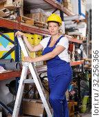 Female in uniform and helmet standing at steps and choosing construction materials. Стоковое фото, фотограф Яков Филимонов / Фотобанк Лори