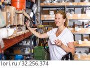 Woman holding shop list and choosing tools at shelves in build store. Стоковое фото, фотограф Яков Филимонов / Фотобанк Лори