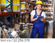 Young woman in uniform looking construction materials with notebook and basket. Стоковое фото, фотограф Яков Филимонов / Фотобанк Лори