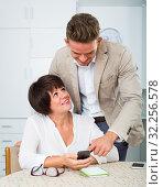 Купить «Son telling brunette mother how to use phone», фото № 32256578, снято 9 декабря 2019 г. (c) Яков Филимонов / Фотобанк Лори