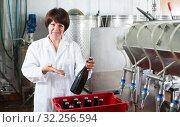 Купить «Attentive female employee packing wine bottles», фото № 32256594, снято 10 ноября 2016 г. (c) Яков Филимонов / Фотобанк Лори