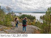 Купить «Туристы фотографируют Ладожское озеро со скалы Руллалахденвуори на острове Кильпола. Карелия», фото № 32261650, снято 22 сентября 2018 г. (c) Румянцева Наталия / Фотобанк Лори