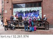Купить «People stand near Stockmann's Christmas window. Traditional puppets installation of Stockmann store. Interactive window display with moving figures in December. Helsinki, Finland», фото № 32261974, снято 29 декабря 2018 г. (c) Кекяляйнен Андрей / Фотобанк Лори