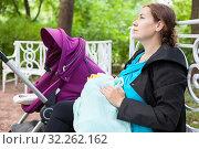 Молодая мама кормит грудью малыша в парке, прикрыв его одеялом, сидит на скамейке возле коляски. Стоковое фото, фотограф Кекяляйнен Андрей / Фотобанк Лори