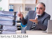 Купить «Aged male employee unhappy with excessive work», фото № 32262634, снято 15 марта 2019 г. (c) Elnur / Фотобанк Лори