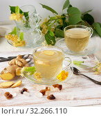 Купить «Transparent cup of herbal linden tea and pieces of ginger on a white wooden board, next to pieces of sugar and twigs with green leaves.», фото № 32266110, снято 7 июня 2019 г. (c) easy Fotostock / Фотобанк Лори