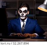 Купить «Businessman with scary face mask working late in office», фото № 32267894, снято 9 ноября 2017 г. (c) Elnur / Фотобанк Лори