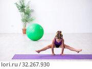 Купить «Little girl gymnast doing exercises indoors», фото № 32267930, снято 16 июля 2019 г. (c) Elnur / Фотобанк Лори
