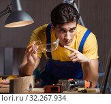 Купить «Worker working in repair workshop in woodworking concept», фото № 32267934, снято 11 августа 2017 г. (c) Elnur / Фотобанк Лори