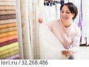Купить «Customer posing near cloth rolls», фото № 32268486, снято 25 января 2020 г. (c) Яков Филимонов / Фотобанк Лори