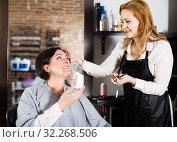 Купить «Young hairdresser working in salon», фото № 32268506, снято 7 марта 2017 г. (c) Яков Филимонов / Фотобанк Лори