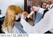 Купить «Hairdresser leveling and cutting hair to young blonde woman with use of scissors», фото № 32268510, снято 7 марта 2017 г. (c) Яков Филимонов / Фотобанк Лори