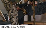 Trainer helping powerlifter to binding his leg by a elastic bandage. Стоковое фото, фотограф Константин Шишкин / Фотобанк Лори