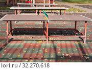 Купить «Желтые опавшие листья лежат на площадке для настольного тенниса и на теннисных столах. Солнечный яркий осенний день в московском дворе», фото № 32270618, снято 8 октября 2019 г. (c) Наталья Николаева / Фотобанк Лори