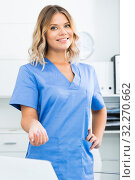 Купить «Friendly girl in doctor's uniform smiling at office», фото № 32270662, снято 17 октября 2017 г. (c) Яков Филимонов / Фотобанк Лори