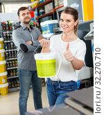 Купить «Young woman standing near man and holding bucket of paint in household store», фото № 32270710, снято 17 мая 2018 г. (c) Яков Филимонов / Фотобанк Лори