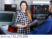 Young woman is satisfied of tire replacement of her car in spring. Стоковое фото, фотограф Яков Филимонов / Фотобанк Лори