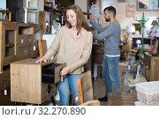 Купить «Girl choosing vintage bedside table», фото № 32270890, снято 9 ноября 2017 г. (c) Яков Филимонов / Фотобанк Лори