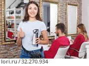 Купить «Young female hairstylist standing in salon, clients on background», фото № 32270934, снято 25 апреля 2018 г. (c) Яков Филимонов / Фотобанк Лори