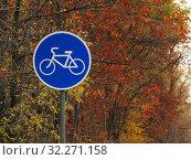 """Купить «Знак """"Велосипедная дорожка"""" на фоне осенних деревьев в парке», эксклюзивное фото № 32271158, снято 9 октября 2019 г. (c) Елена Осетрова / Фотобанк Лори"""