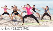 Купить «Sporty people practicing yoga on beach», фото № 32275942, снято 14 июня 2017 г. (c) Яков Филимонов / Фотобанк Лори