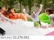 Game of funny friends in soap suds on an inflatable trampoline. Стоковое фото, фотограф Яков Филимонов / Фотобанк Лори