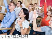 Купить «Students sitting with hands raised during lesson», фото № 32276074, снято 21 октября 2019 г. (c) Яков Филимонов / Фотобанк Лори