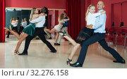 Купить «Positive adult pairs enjoying dancing in modern dance studio», фото № 32276158, снято 4 октября 2018 г. (c) Яков Филимонов / Фотобанк Лори