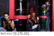 Купить «Smiling friends playing laser tag game with laser guns in labyrinth», фото № 32276202, снято 23 августа 2018 г. (c) Яков Филимонов / Фотобанк Лори