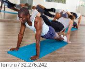 Купить «Women and men exercising in pairs during yoga class in modern fitness center», фото № 32276242, снято 30 июля 2018 г. (c) Яков Филимонов / Фотобанк Лори