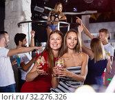 Купить «smiling women dancing in the night club with drinks in the hand», фото № 32276326, снято 28 августа 2017 г. (c) Яков Филимонов / Фотобанк Лори