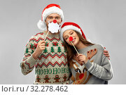 Купить «couple with christmas party props in ugly sweaters», фото № 32278462, снято 9 декабря 2018 г. (c) Syda Productions / Фотобанк Лори
