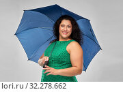 Купить «happy woman in green dress with blue umbrella», фото № 32278662, снято 15 сентября 2019 г. (c) Syda Productions / Фотобанк Лори