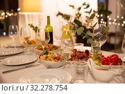 Купить «table served with plates, wine glasses and food», фото № 32278754, снято 15 декабря 2018 г. (c) Syda Productions / Фотобанк Лори