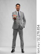 Купить «man realtor with house model and folder», фото № 32278854, снято 8 сентября 2019 г. (c) Syda Productions / Фотобанк Лори