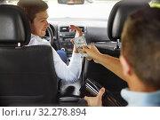 Купить «male car driver looking at passenger with money», фото № 32278894, снято 25 августа 2019 г. (c) Syda Productions / Фотобанк Лори
